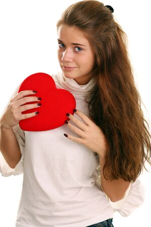 Portrait of a charming young girl on a white background holding a heart  photo