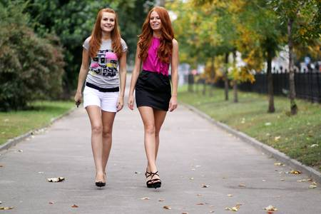 happy young women walking in summer park photo