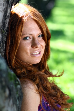 Portrait of red-haired beautiful young woman, against green of summer park.  photo