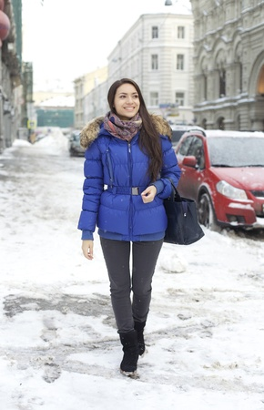 Caucasian young adult female smiling and walking down snow covered street photo