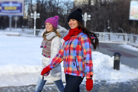 Happy young couple women in winter street photo