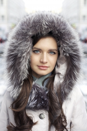 Portrait of a young woman on the background of a winter city photo