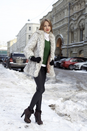 Caucasian young adult female smiling and walking down snow covered street