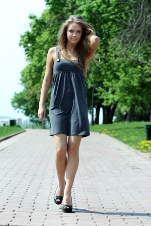 Beautiful young woman walking on the street  photo