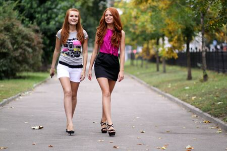 autumn city: Happy two young women in autumn city