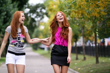 Happy two young women in autumn city photo