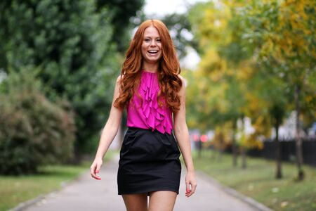 Happy young woman in autumn city photo