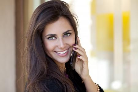 llamando: Mujer feliz joven que llama por el tel�fono en la calle