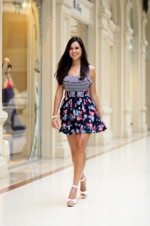 Beautiful young woman walking in the shop