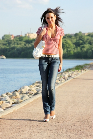 Full length portrait of a young lady walking outdoor