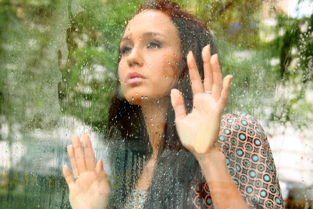 Portrait of a young woman near the window after the rain Standard-Bild
