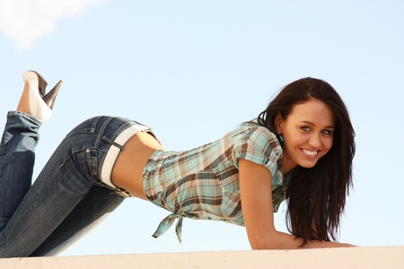 Young woman in blue jeans and cell shirt photo