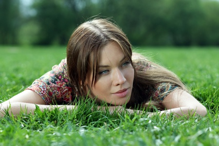 Portrait of young woman lying on a green lawn photo