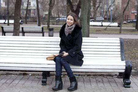 sits: Beautiful young city woman sits on a bench Stock Photo