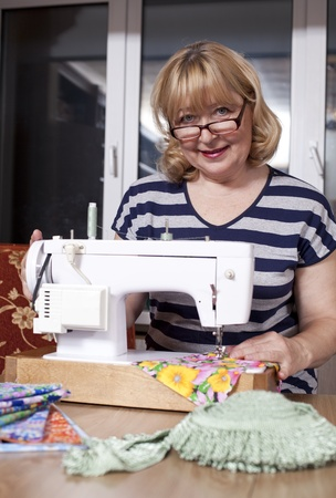 Old woman sews on the sewing machine photo