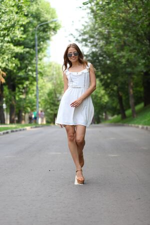 Beautiful young woman walking on the summer park photo