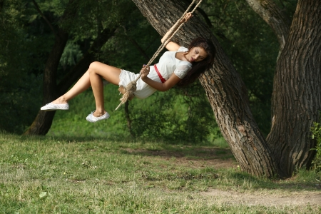 Young happy woman riding on a swing in the park photo