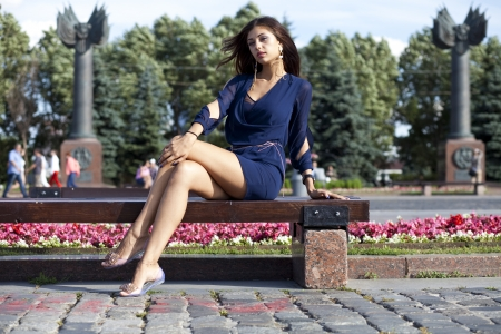Beautiful young woman sits on a bench  photo