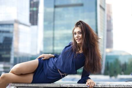 Young woman in a blue dress is stretching near skyscrapers  photo