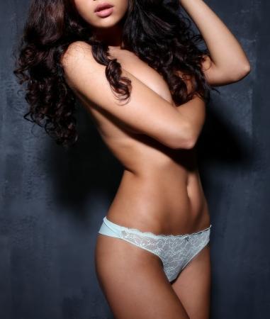 bikini wear: Sexy female body in white underwear on a dark wall