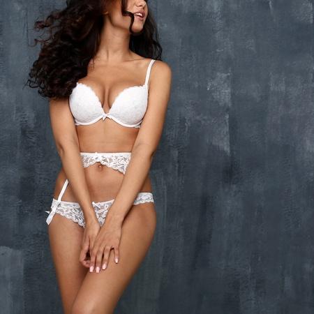 girl bra: Sexy female body in white underwear on a dark wall