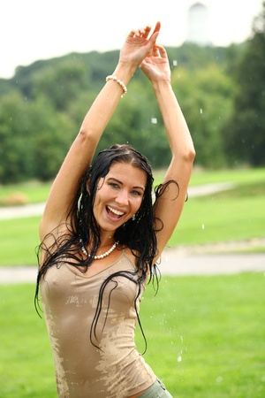 Young happy woman walking in the rain photo