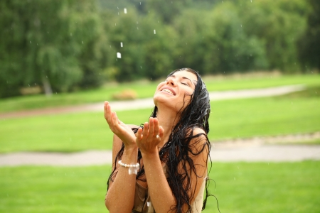 Young happy woman walking in the rain photo