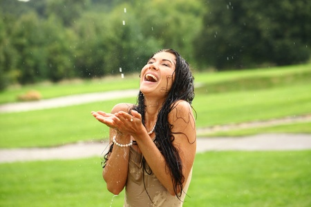 Young sexy brunette woman outdoor in a garden playing with water and rain with wet shirt