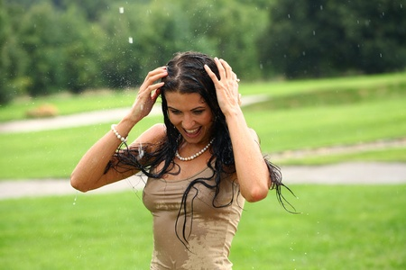 Young sexy brunette woman outdoor in a garden playing with water and rain with wet shirt photo