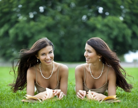 Twins young women reading a book outdoor  photo