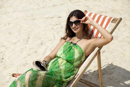 Mujer hermosa joven relajante acostado en una tumbona