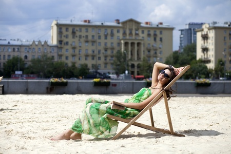 Young beautiful woman relaxing lying on a sun lounger photo