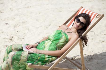 Young beautiful woman relaxing lying on a sun lounger photo
