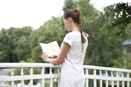 Brunette reading book in a summer park photo