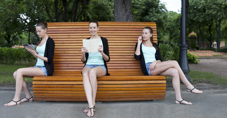 Three young women on a summer park bench  photo