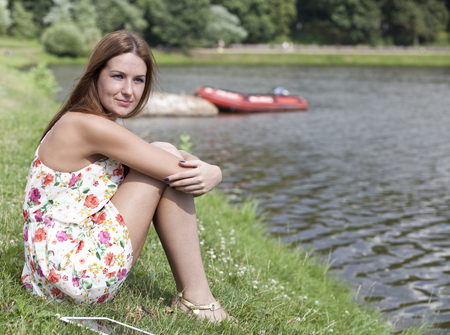 Portrait of a beautiful woman sitting on a lakes shore    photo