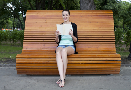 Brunette sitting on a bench in a summer park photo