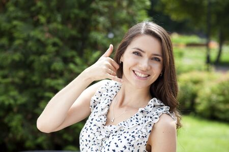 call me: Portrait of attractive young woman on open air  Woman making a call me sign outdoors Stock Photo
