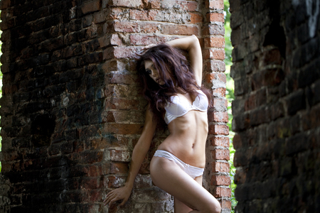 underclothes: Portrait of sexy woman in white underwear on a brick wall Stock Photo