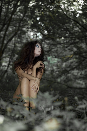 Mysterious naked girl sitting in a dark forest photo