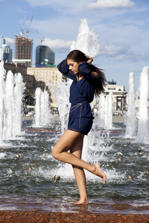 Young sexy woman in a city fountain  photo