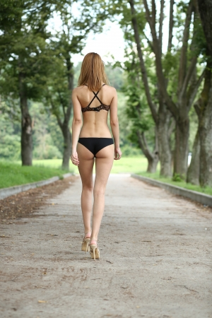 Beautiful young woman walking on the summer park Stock Photo