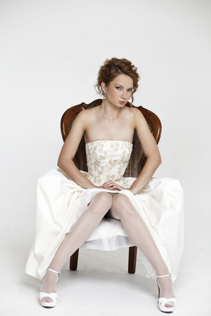 sits on a chair: Portrait of the young beautiful bride