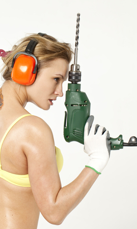 bikini construction: Young sexy woman holding a construction drill Stock Photo