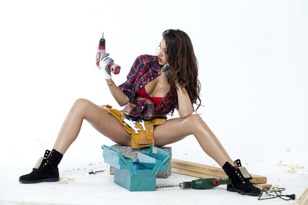 Sexy young woman sits on a brick builder building tools near photo