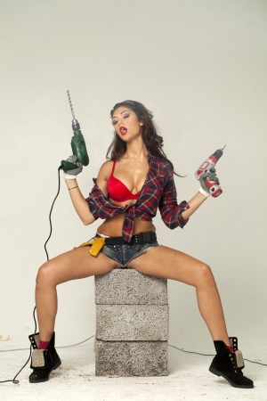 High fashion glamour model in Daisy duke shorts, tool belt, red bra with a screw gun  Foto de archivo