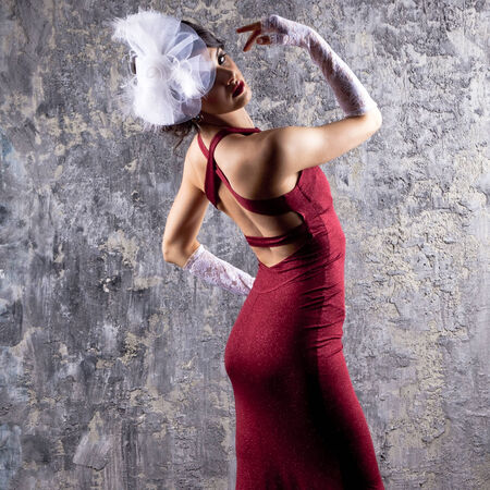 Young beautiful caucasian brunette in long red gown posing on dark wall   photo