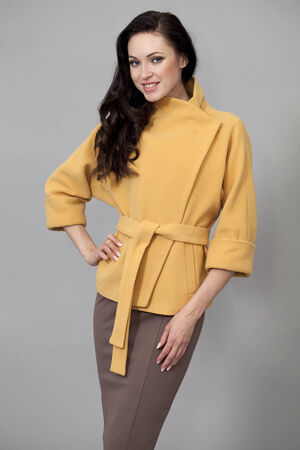 Beautiful young woman in yellow coat against grey wall photo