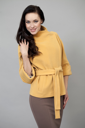 Beautiful young woman in yellow coat against gray background photo