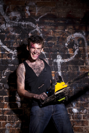 petrol powered: horrific madman on a dark background and gasoline-powered saw